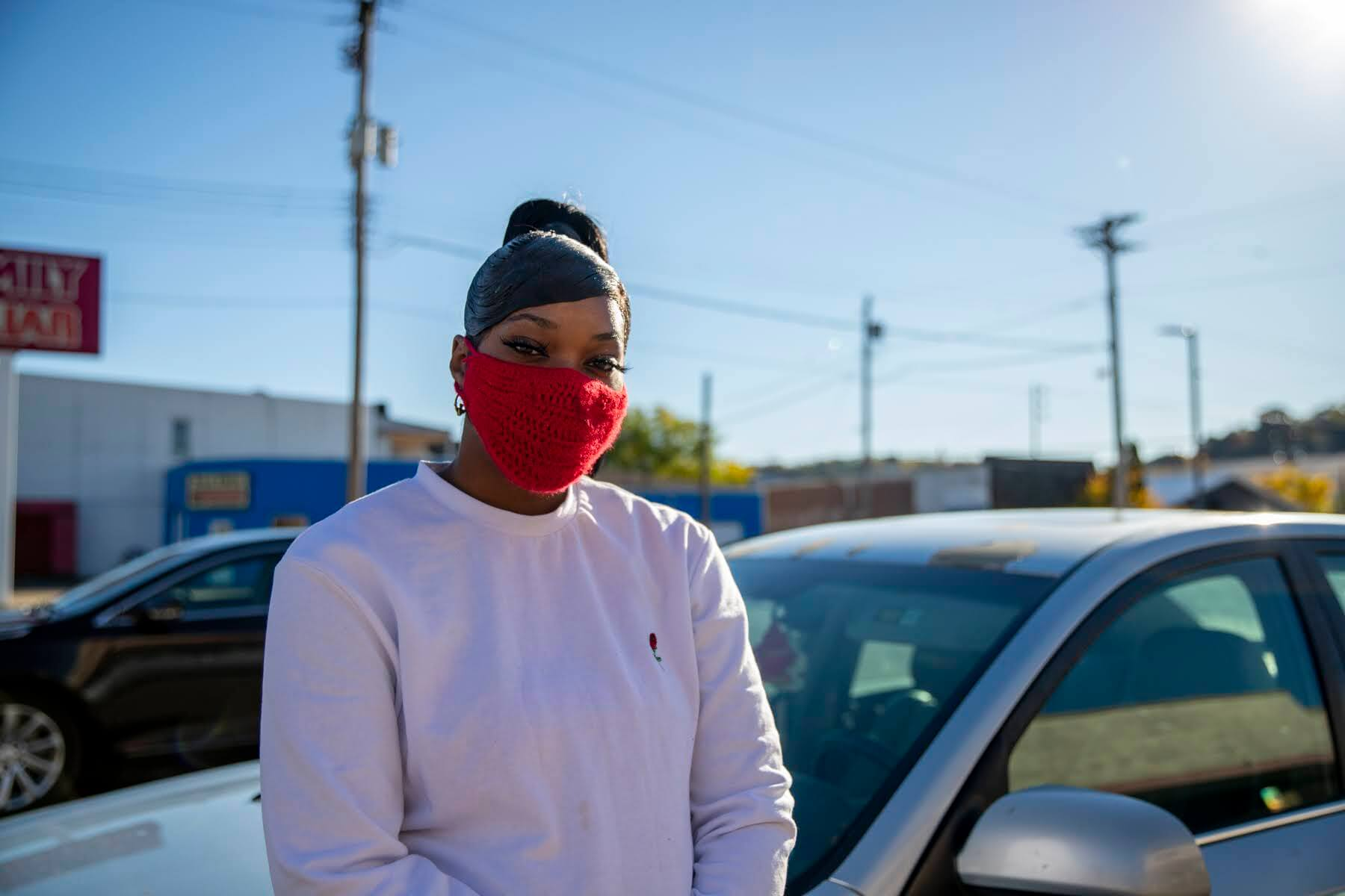 Shadawn Reeves, a Glassport resident, masked standing in front of car.