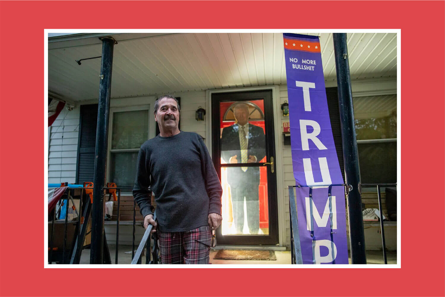 Barry McGuane in a gray shirt standing on his porch next to a TRUMP NO MORE BULLSHIT vertical blue banner and in front of a cut out life size photo of Donald Trump.